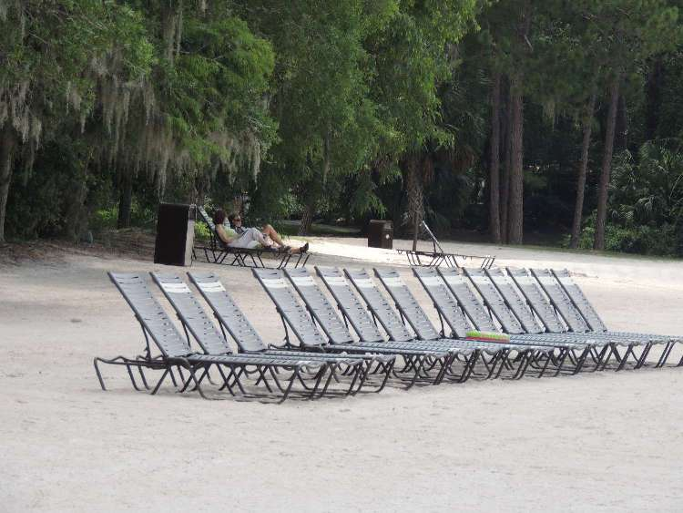 Relax in a lounge chair on the beach at Disney's Fort Wilderness Resort & Campground