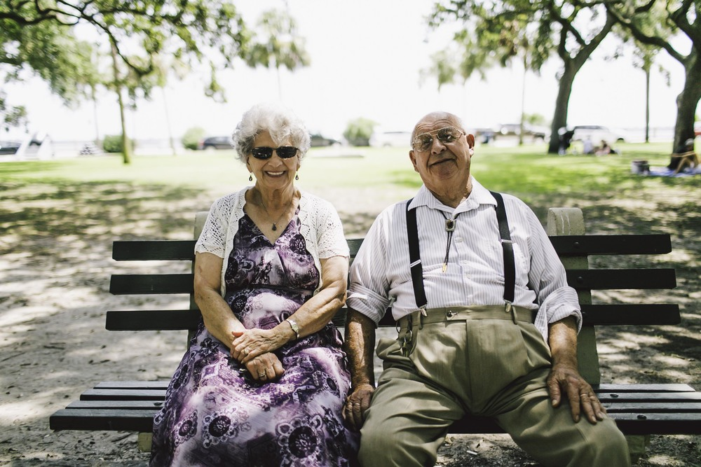 "Christine Dewer and Melvin Pace.  They were sitting on this park bench in Downtown Charleston.  They sat there as if they had done so every day since the beginning of time.  I imagined them as the center of a time lapse video. I imagined them sitting on that bench without a care in the world as time, as well as everything and everyone, sped around them.  These two were no less stoic than the legacy oaks that were deeply rooted throughout the park they sat in.   I asked I could take their photo and they happily agreed.  It was only after Michele and I approached them, that it seemed they were brought back to the ""real world"" and they were eager to talk."