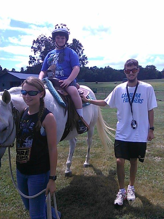 Paul at age 20 volunteering as a sidewalker during a therapeutic riding session.