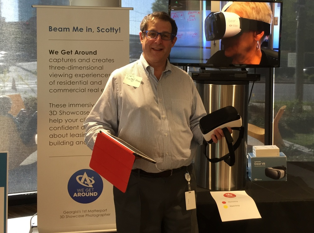 "We Get Around Founder, CEO and Chief Photographer Dan Smigrod at a Matterport Spaces (3D, VR) demo event. The shopping list below, includes the following items above: (left to right): Retractable banner; iPad Air 2, Gear VR, Samsung Galaxy 7 smartphone; Insignia 48"" TV; Samsung Blu-ray TV; pedestal; HDMI cable. Other items not pictured: DVD burner; recordable DVDs; extension cord; power strip; duct tape; alcohol sterilizing pads and luggage cart."