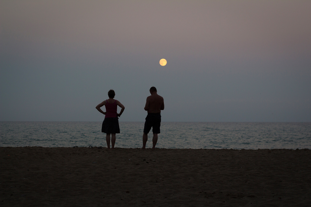 A couple watch the moon rise over the beach.