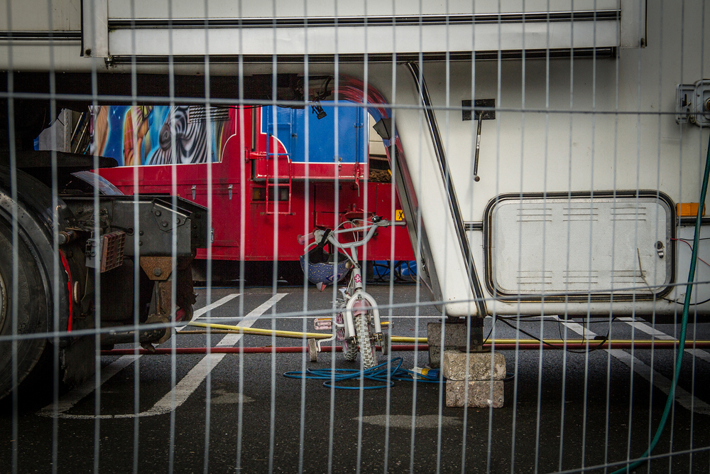 A circus child's bicycle under a trailer.