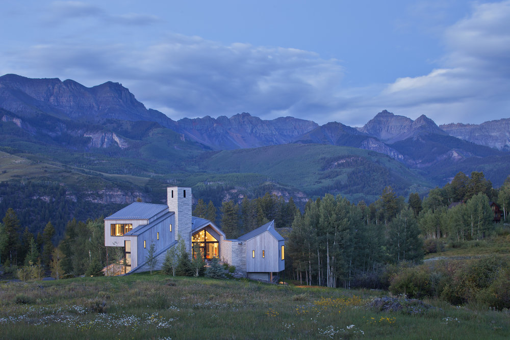 Architect Tommy Hein creates a modern masterpiece in Mountain Village. Inspired by its former use as a ranch and the nearby barn relic. Due to its unique location close to the rim overlooking the valley, the mountains are very close and panoramic. To capture the views, the entire house is radial about a single point in space to the south of the dining area. Windows were carefully positioned to screen the road, yet open to the views and open space like petals of a flower.