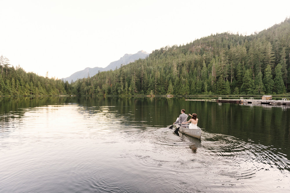 Couple canoeing on a lake with mountain views