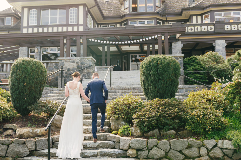 Couple walking up steps with a house in the background