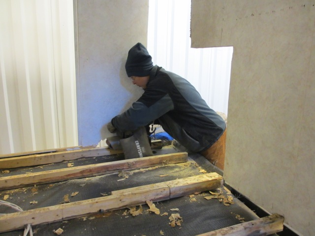 Sanding each of the joists so the new sub-floor has something flat and even to lay on.