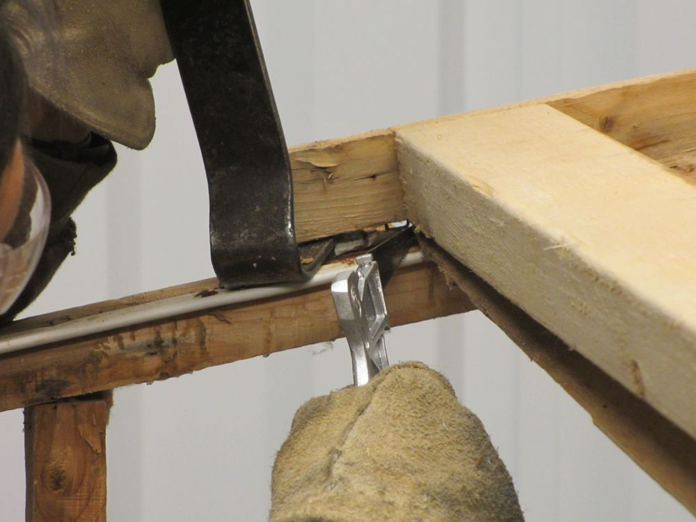 There is luan stapled and sandwiched between the roof beams that we removed using a pry bar and small hand saw.
