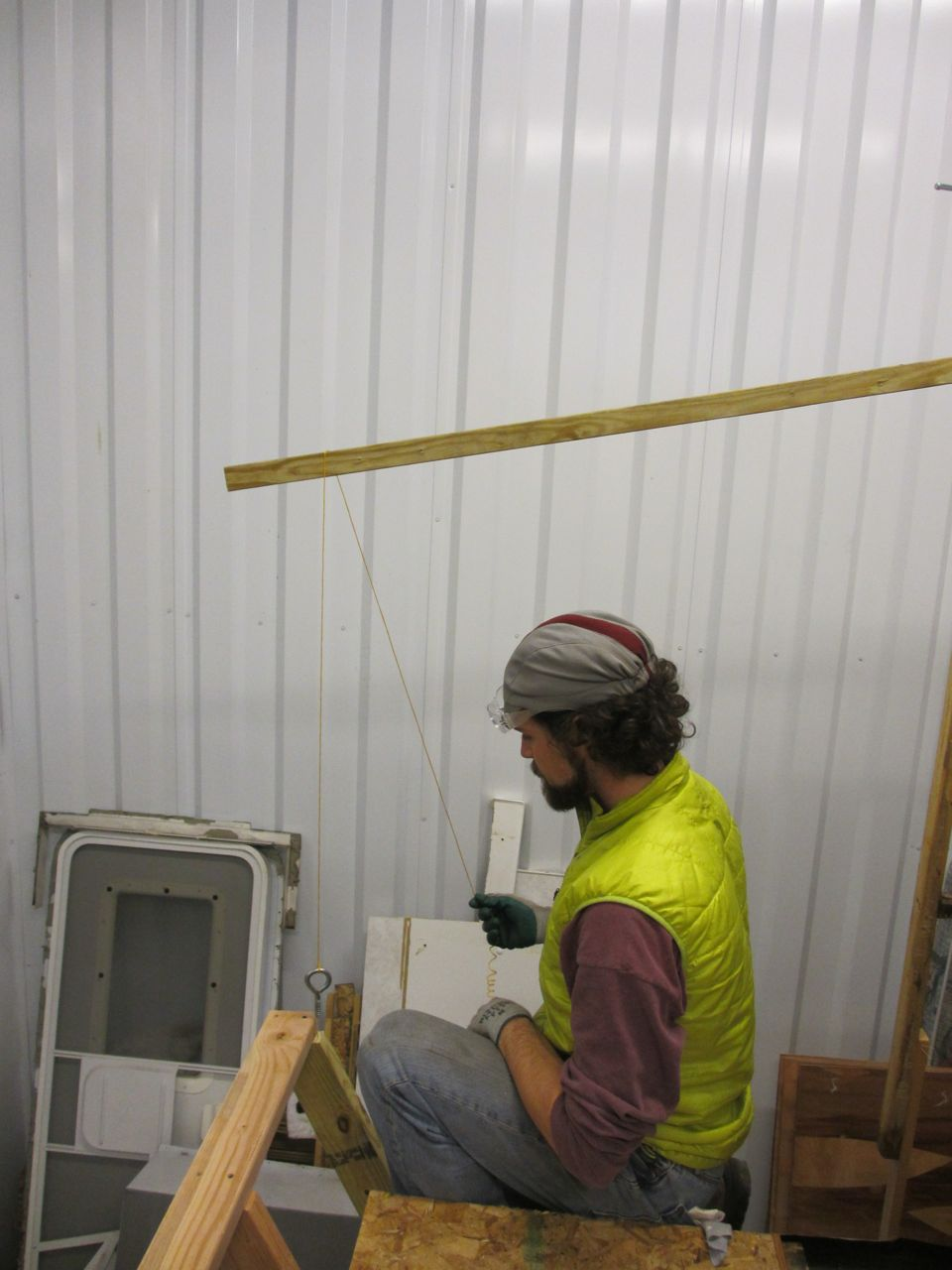 Jerud sets up a plumb bob to see where the roof stud extension needs to end to meet the front wall stud.