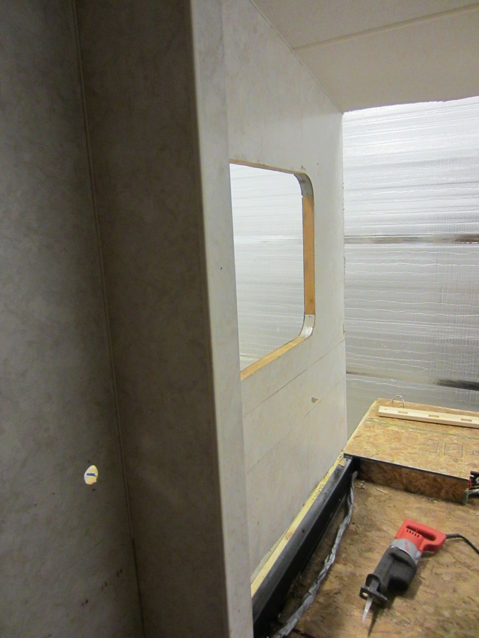 Divider wall between the bedroom and the bathroom sink on the driver side of the trailer.