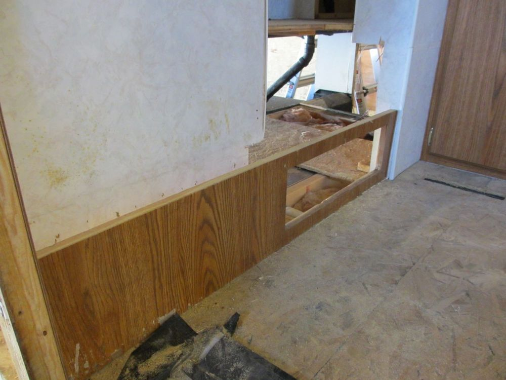 Behind the wood board with the rectangular hole is the inside of the basement.