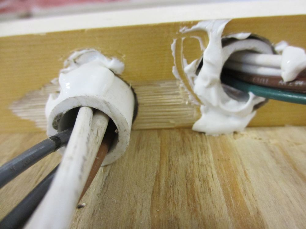 To ensure the wires don't rub against the wood and potentially get cut, we placed pieces of PVC pipes in-between them and the wood.