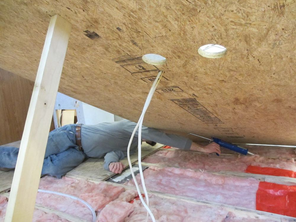Using a beam to hold up the sub-floor so Jerud could put Liquid Nails down and I can take photos.