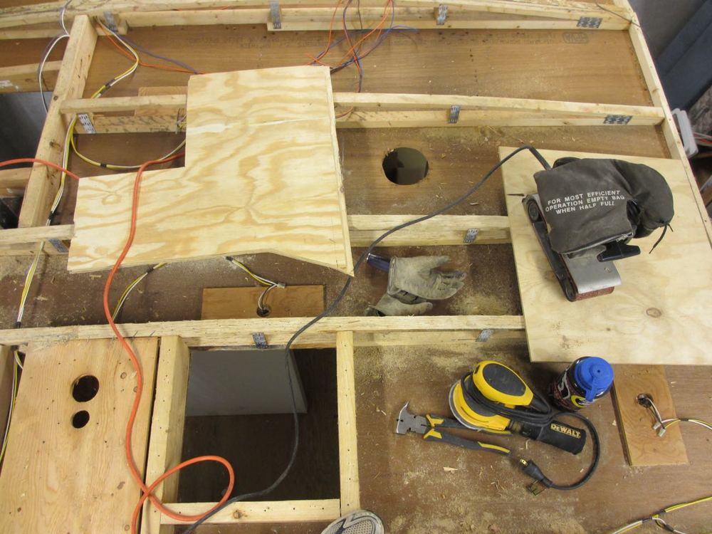 Set up on the roof to be able sand the roof beams down. The weird shape board is used to sit/kneel on when sanding.