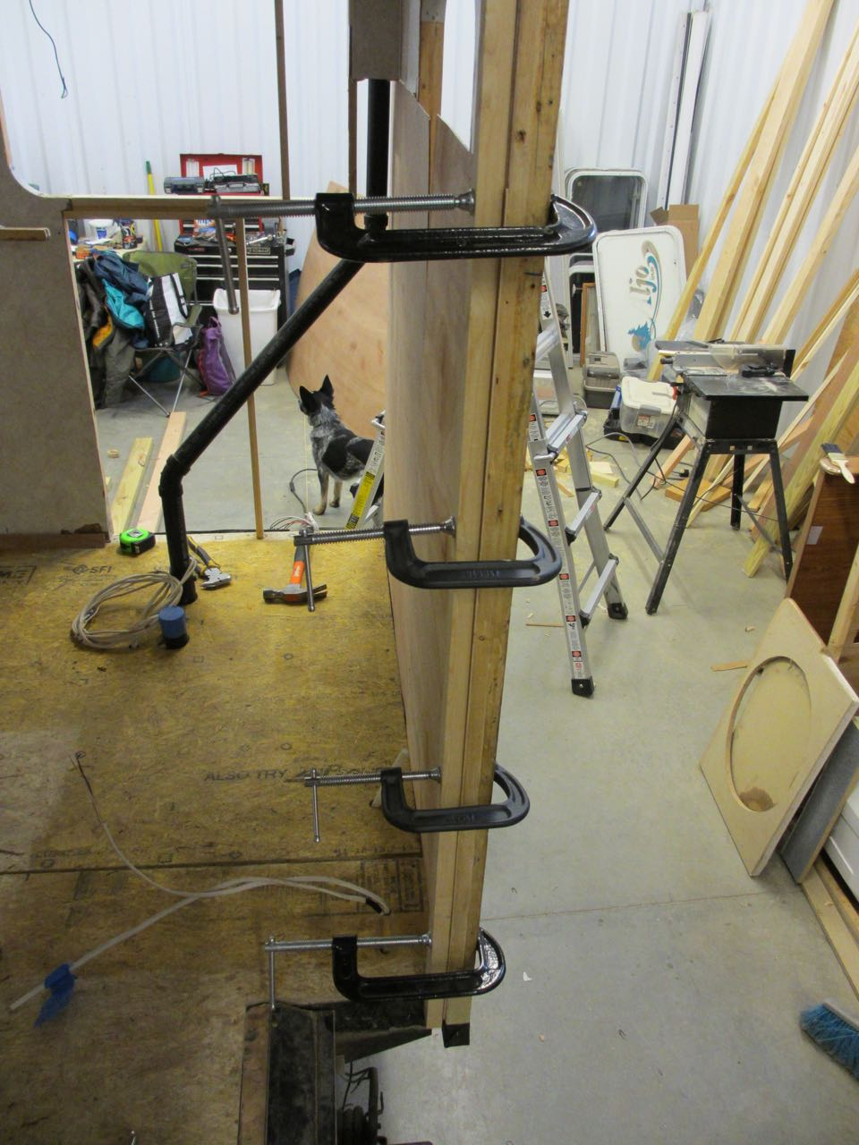 Clamps held the luan against the beams overnight to ensure it was glued tightly.