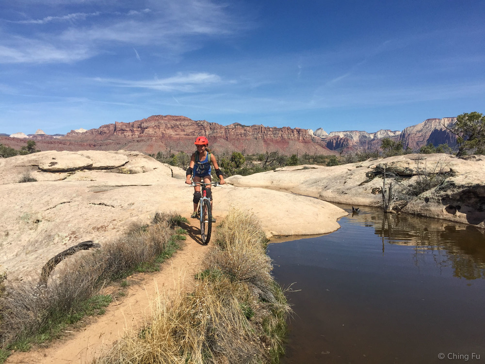 Sarah riding next to a pond that randomly shows up on the trail. Yes, that's Zion in the background.