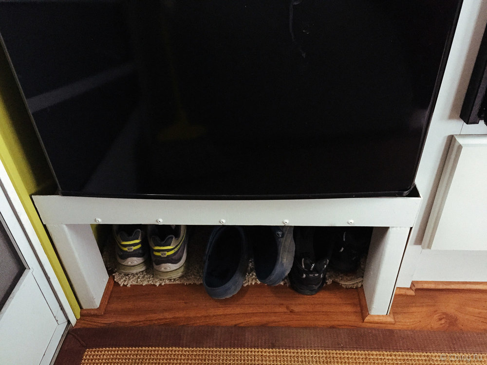 Shoe storage under the fridge.