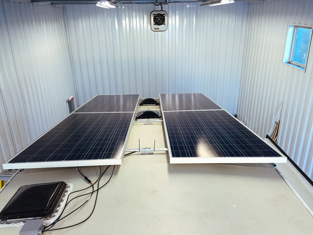 Four 305 watt solar panels installed on the rack.