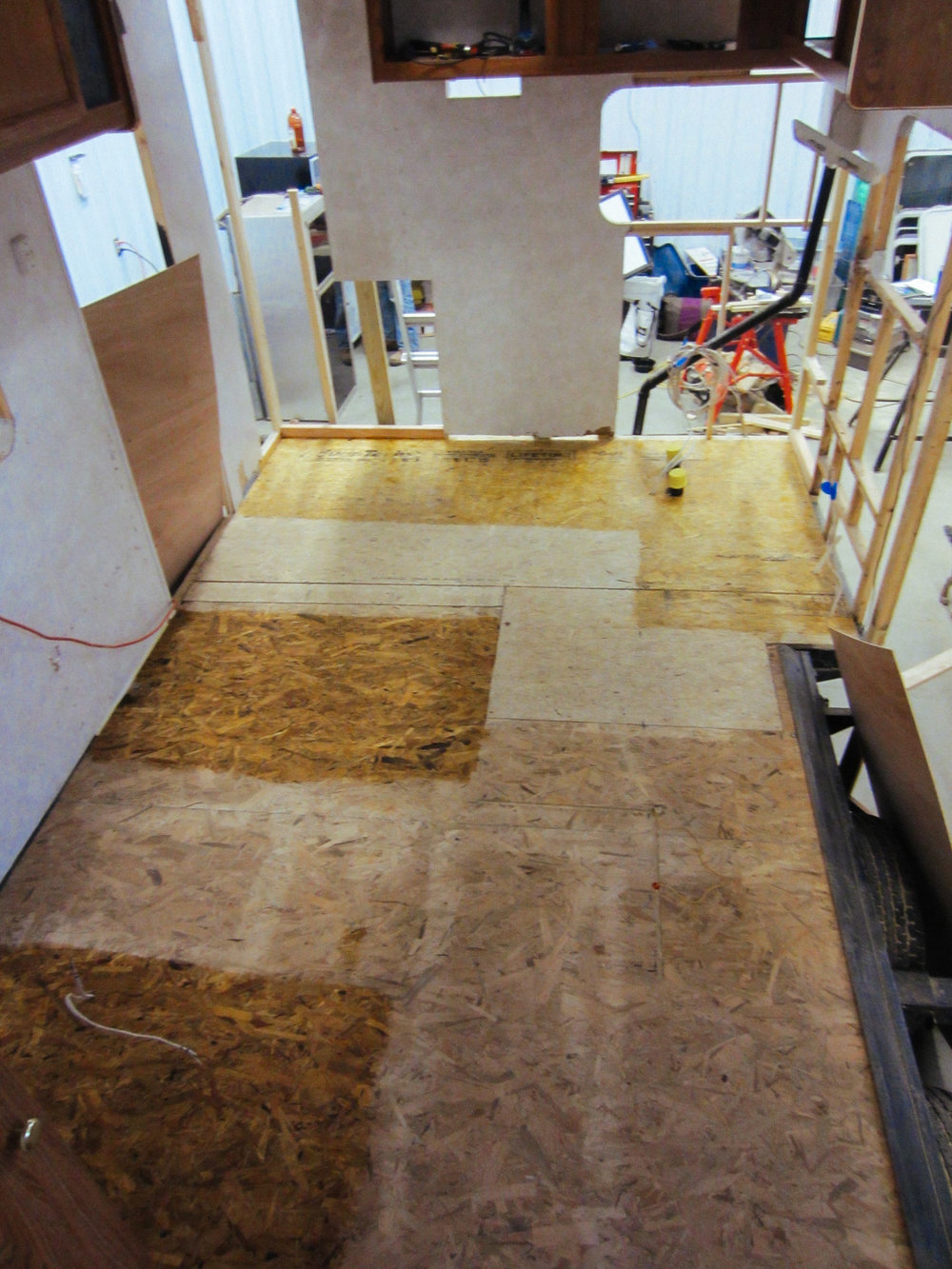 We applied polyurethane to the sections of the sub-floor that wouldn't have laminate floors installed over them. This is where the kitchen cabinet, dinette seats, and the couch are.