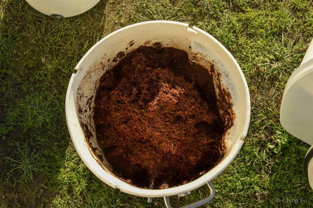 Adding coco pith to our recently emptied out composting toilet.
