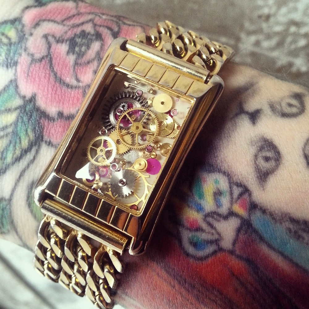 This vintage watch has been gutted and revamped into a stylish one of a kind bracelet containing multiple layers of resin cast watch parts over a hand painted background.