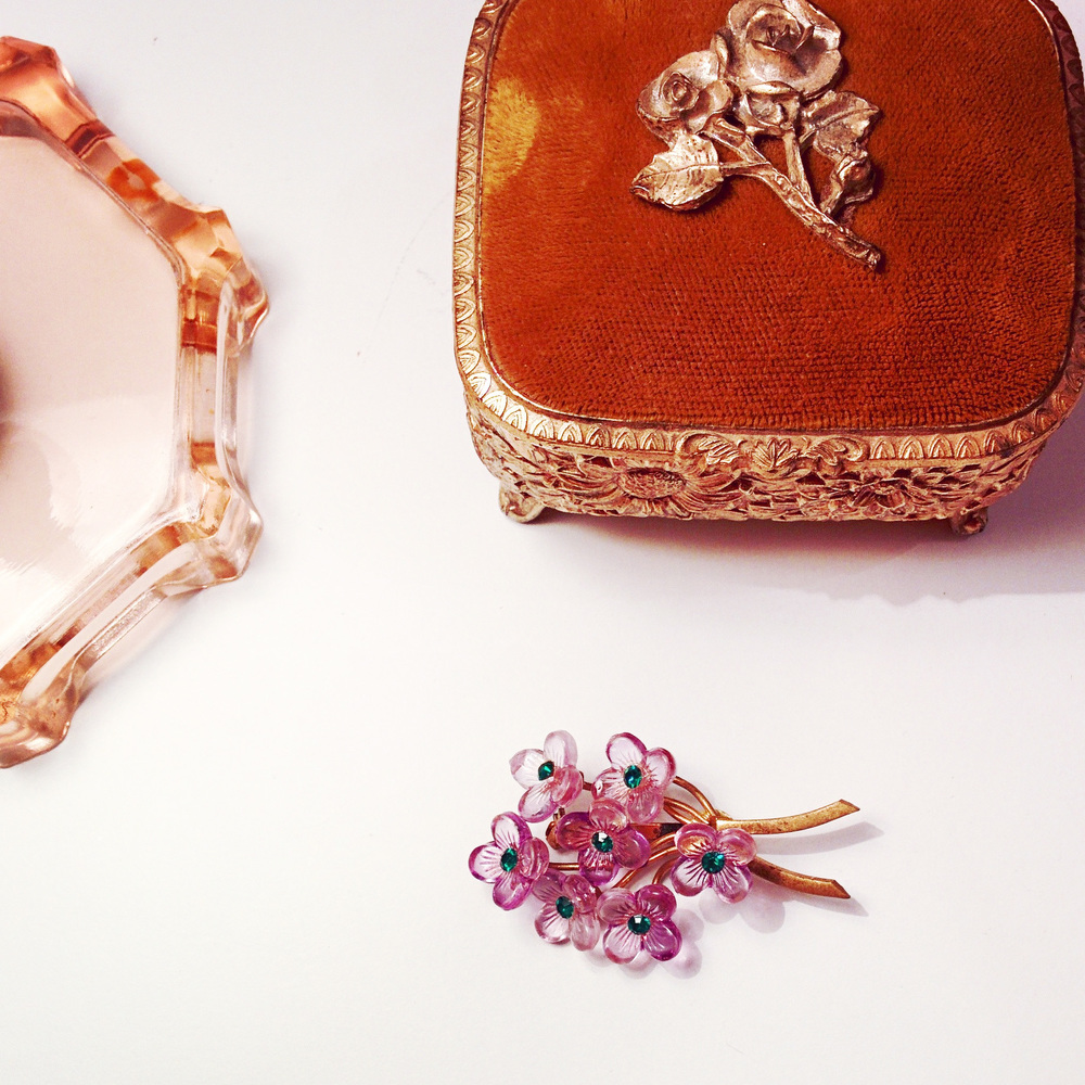 Love this violet floral brooch with green rhinestone detail!