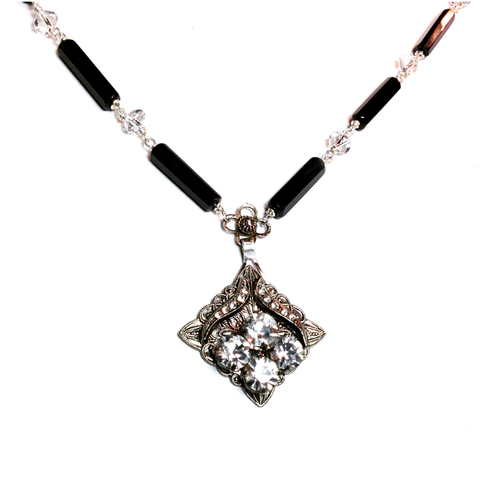 A lovely modified rhinestone treasure with plenty of detail sits on a small vintage flower and a chain made of onyx and crystal quartz
