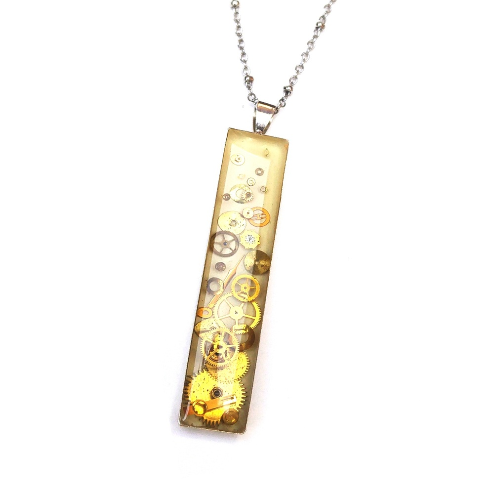 This deep set rectangular watch part pendant has more layers than your average resin pendant! It is composed entirely of old golden watch parts, highlighted by the hand painted white background.