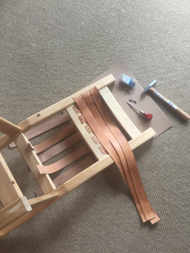 Leather strips nailed to the FRONT of the chair frame