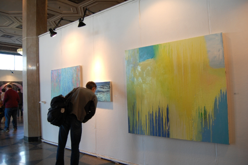 A viewer studies  Cape Ann coast , at the 2014 BU painting thesis show.