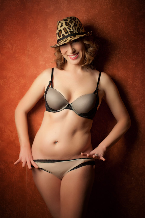 Fedora Hat Boudoir on red wall.