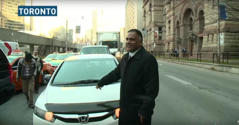 Cab driver pounds on UberX car, dragged 20 metres in Toronto protest. Photo: cbc.ca