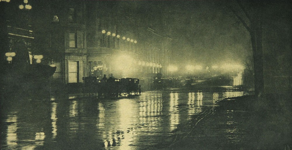 "Alfred Stieglitz, The Glow of Night — New York, Photogravure: Multiple Color, 1897.  Photographed in 1897 Manhattan, this nighttime view shows the Savoy Hotel with a queue of carriages along a rain-slicked Fifth Ave. The nighttime ""glow"" effect in this print is achieved in the printing process."