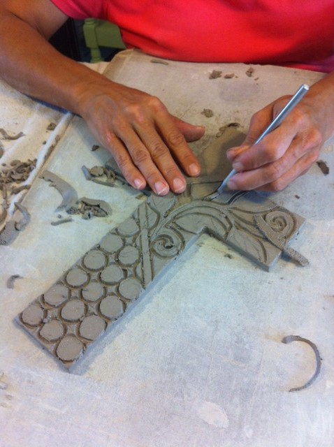 Clare carving out the clay for one of our crosses.