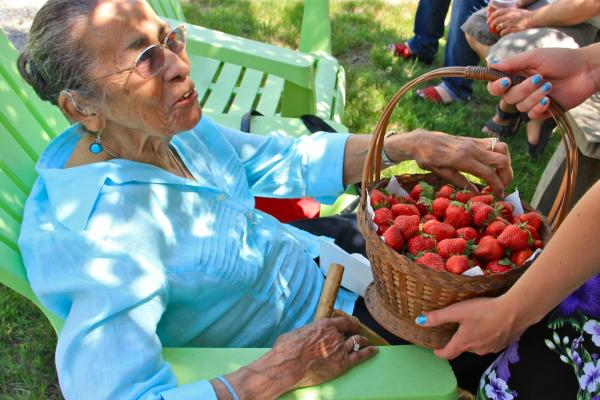 Eleanor Spears Dove, 97, Narragansett elder, sampled a strawberry from a basket passed at the Narragansett Strawberry Thanksgiving.
