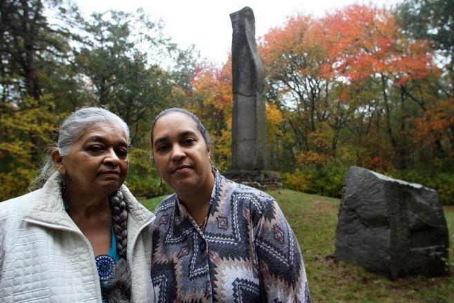 Paulla Dove Jennings, left, and Loren Spears, next to the Great Swamp Massacre Monument in South Kingstown. The Providence Journal/Bob Breidenbach