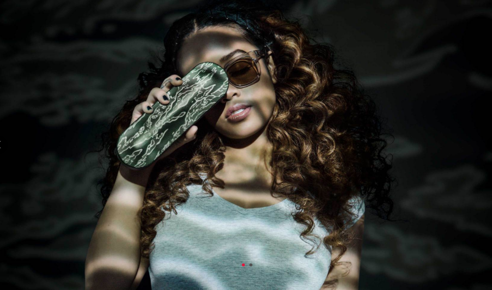 H.E.R.  getting playful with the Beats / UNDEFEATED Pill+ speaker.