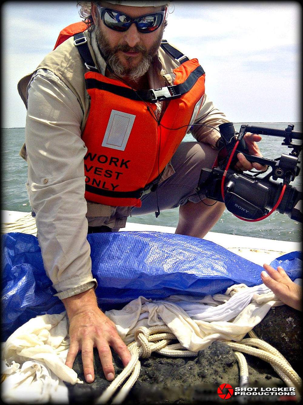 "During a brief break in filming, Sean Paxton, on board the dive barge, ""Jones Bay"" admires one of Blackbeard's cannon balls during a recovery expedition and production in Beaufort, NC. This concretion pile containing several cannon balls and numerous other artifacts was raised from the wreck site of Blackbeard's flagship, the Queen Anne's Revenge, which sank off Beaufort in 1718."
