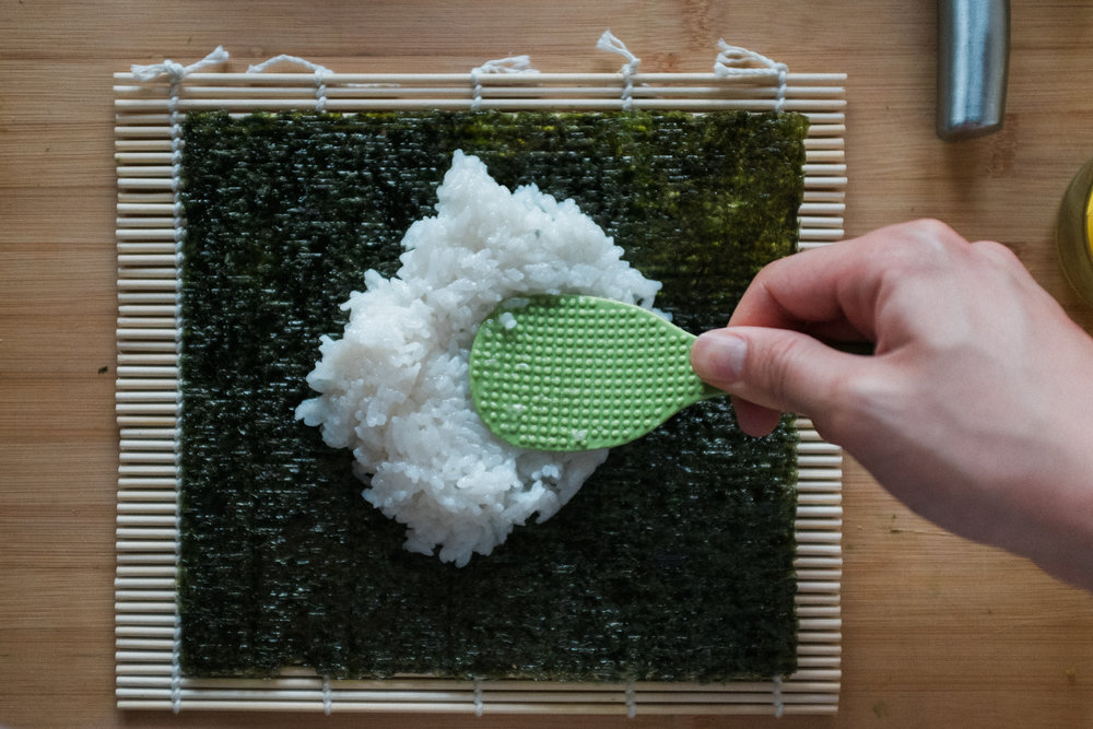 Put nori sheet on sushi mat and spread rice. Keep rice warm to make spreading easy.