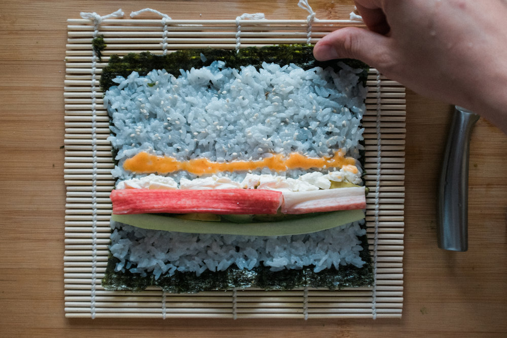 Add ingredients ¼ of the way up and wet the far edge of the nori sheet.