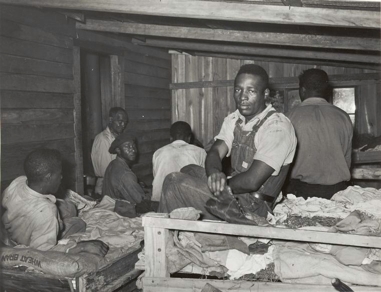 Negroes in bunkhouse in strawberry fields near Hammond, Louisiana; Note crude bunks, straw mattresses, and crowded conditions, April 1939. From the New York Public Library.