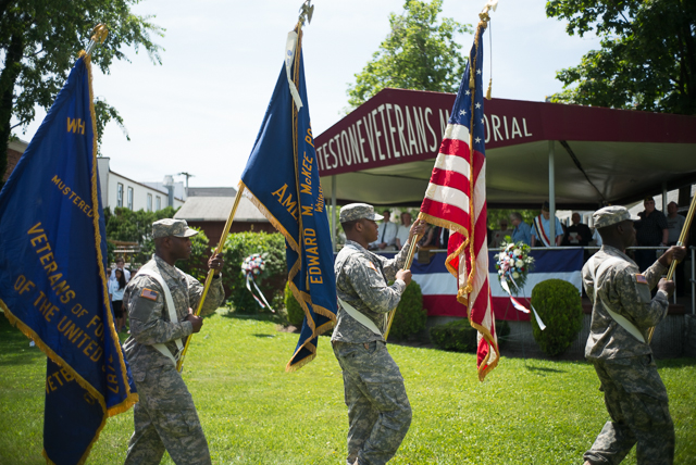 Soldiers present the flag before the start of the Whitestone Memorial Day Parade.