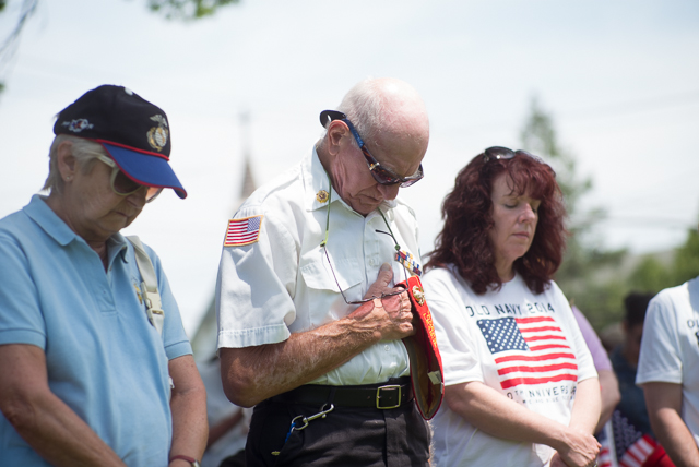 Visitors pray in rembrance during the opening ceremony of the Whitestone Memorial Day Parade.