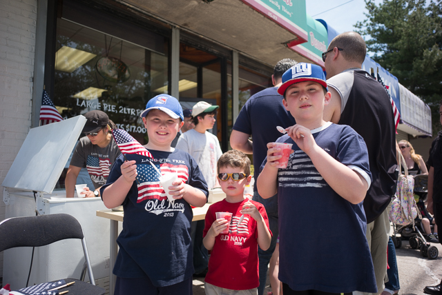 Brothers Dylan Ehrmann, 7, Luke Ehrmann, 4, and John Ehrmann, 9, enjoy italian ices outside Mike & Maggie's Pizzeria at the Whitestone Memorial Day Parade.