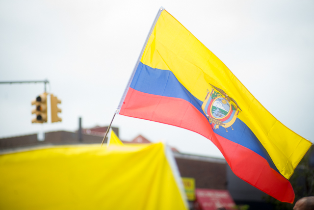 The Ecuadorian flag waves above Northern Blvd. during a parade Sunday. Photo by Ken Maldonado