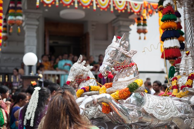 Chrome horses mark the front of a chariot which pulls a figure of the hindu diety Ganesh.