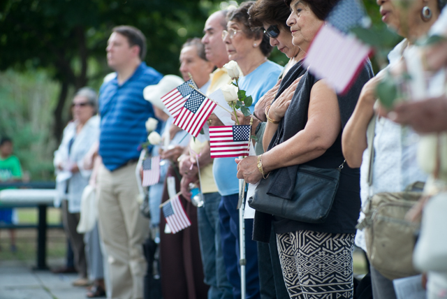 Visitors hold flags as well as white roses tagged with the names of 9/11 victims during a memorial service held in Woodside on the 13th anniversary of the World Trade Center attack. Photo by Ken Maldonado
