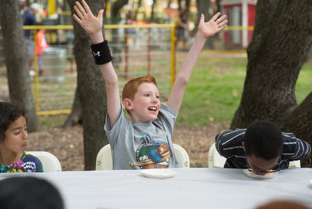 A child raises his hands after finish his plate during a pie eating contest at the Queens County Fair.