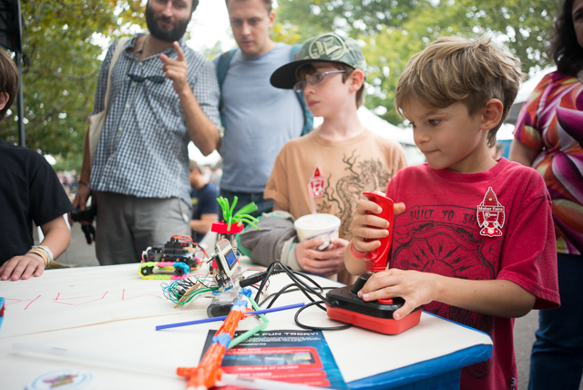 A child plays with a remote controlled robot at a booth at Maker Faire.