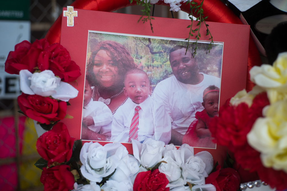 A photograph of Alton Sterling and his family is placed on a memorial outside the Triple S grocery store.