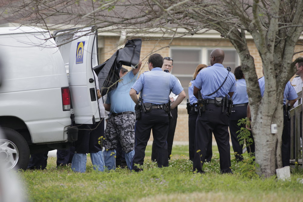 Members of the New Orleans Coroners Office load the body of a child into the coroners van at the scene of a triple homicide in the New Orleans neighborhood of Gentilly where a mother and two children were found shot and killed. A fourth victim, a 12-year-old girl was found still alive at the scene and was transported to an area hospital in critical condition.